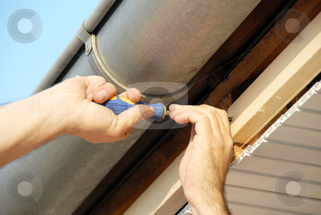 Works on house stock photo, Working hands screwing up under house roof outdoor by Julija Sapic