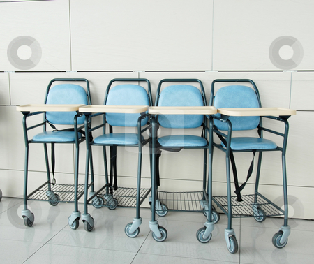 Baby sitting chairs stock photo, Four baby blue sitting chairs in row indoor by Julija Sapic