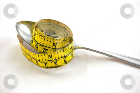Tape Measure on Spoon Dieting stock photo, This still life represents dieting with a tape measure on a silver spoon, isolated on a white background. by Valerie Garner