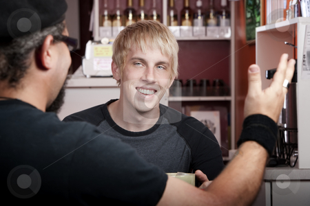 Coffee House Conversation stock photo, Cheerful young blonde man reacting to coffee house conversation by Scott Griessel