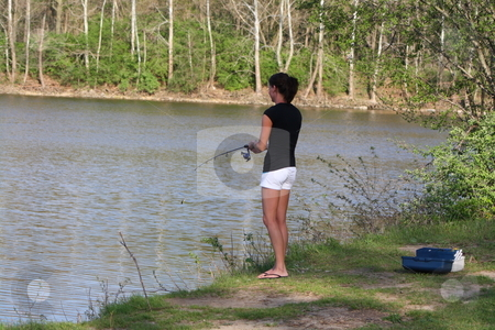 A Beautiful Young Woman Fishing stock photo, Rebeka brings her tackle box and an open reel fishing pole for a day of fishing at the lake. by Chris Torres