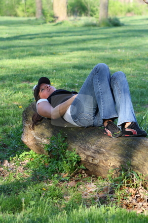 Woman resting on a log stock photo, Rebecca stops to rest and enjoy the warm sunny spring day. by Chris Torres