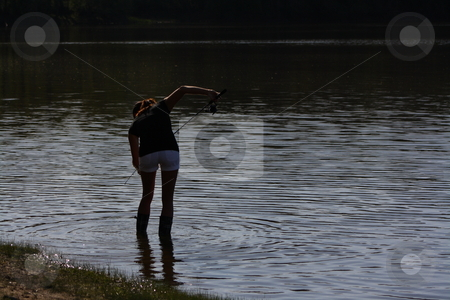 Silhouette of a young woman fishing stock photo, A Young woman wearing boots gets in the water for some night fishing. by Chris Torres