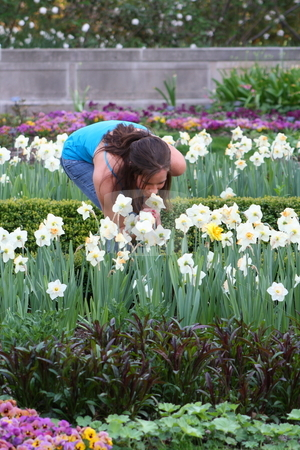Woman enjoying flowers stock photo, Rebecca leans over and enjoys smelling the beautiful flowers. by Chris Torres