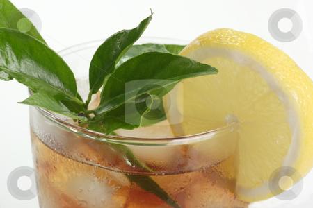 Lemon ice tea stock photo, A glass full of Ice Tea with a lemon slice on bright background by Birgit Reitz-Hofmann