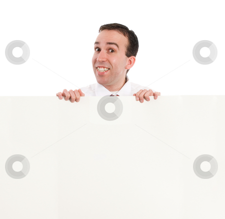 Man Looking Over Wall stock photo, A young businessman smiling and looking over an office wall by Richard Nelson
