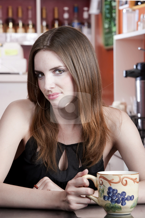 Pretty woman in a coffee house stock photo, Woman with big mug in coffee house by Scott Griessel