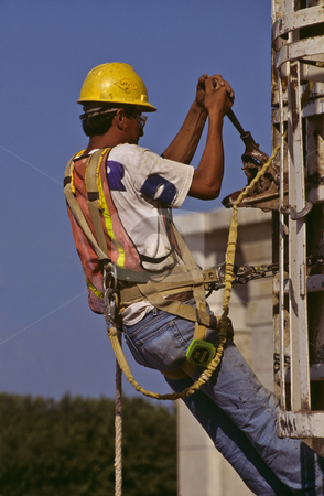 Construction worker adjusts pouring form. stock photo, A harnessed, hardhatted worker hangs from a concrete pillar former while making manual adjustments. by GB Tittle