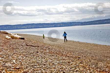 Mom Chasing Little Boy Down the Beach stock photo, This young mom is chasing her young son down the beach to catch up to him.  Beautiful beach scene in Washington state. by Valerie Garner