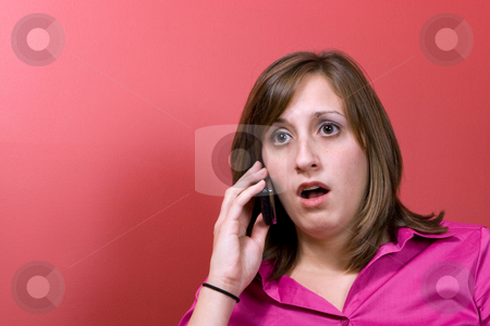 Surprised Woman on the Phone stock photo, A young business woman just heard something that worries her on her cell phone. by Todd Arena