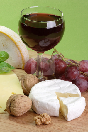 Red wine stock photo, Red wine and cheese on green background by Birgit Reitz-Hofmann