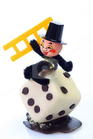 Chimney sweep stock photo, Marzipan chimney sweep with a dice on bright background by Birgit Reitz-Hofmann