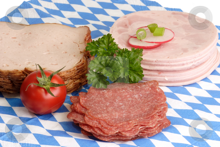 Sliced sausage stock photo, Fresh sliced sausage on bavarian napkin background by Birgit Reitz-Hofmann