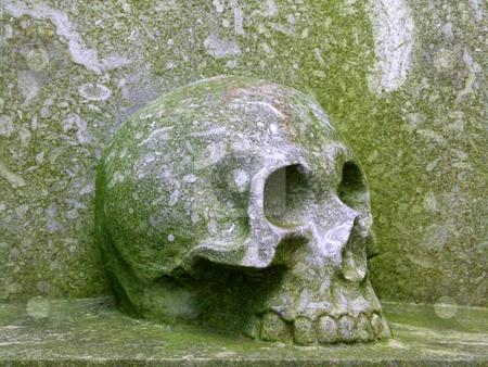 Stone skull stock photo, Old gravestone with a stone skull. by Birgit Reitz-Hofmann