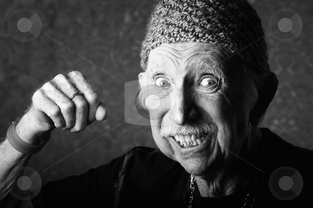 Angry Old Man stock photo, Senior man in knit cap making a fist by Scott Griessel