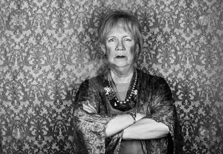 Skeptical Senior Woman stock photo, Portrait of skeptical senior woman in front of gold background by Scott Griessel