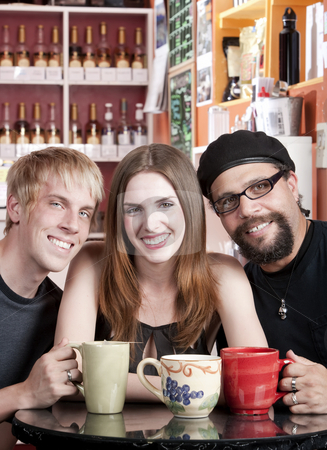 Woman with two male friends in a coffee house stock photo, Three friends posing together in a coffee house by Scott Griessel