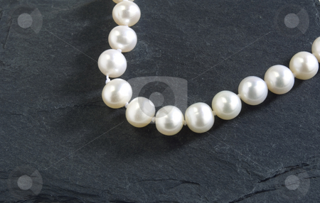 Pearls stock photo, Strand of pearls on a hard slate background by Jonathan Hull
