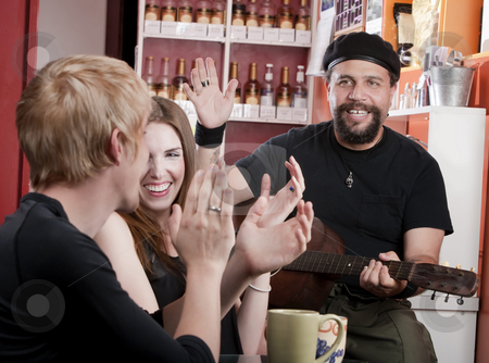 Coffee House Musician stock photo, Couple in coffee house listening to a guitarist by Scott Griessel