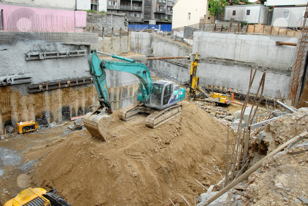 Building site stock photo, Construction site with excavator on earth heap by Julija Sapic