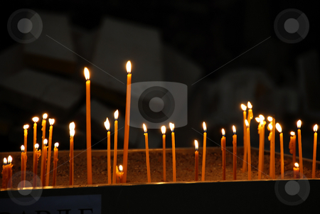 Burning candles stock photo, Yellow candles burning in orthodox church over dark background by Julija Sapic