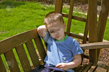 Little Boy Sitting on Garden Swing stock photo, This 4 year old little boy is sitting relaxing on a wooden garden swing.  He is very quiet and still in this photo. by Valerie Garner