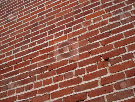 Red Brick Wall stock photo, A red brick wall extends out into the distance. by Ben O'Neal