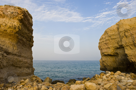 Gap in the mountain showing the sea stock photo, A gap in the mountain forming a small rocky beach with the sea visible in the background. by Nicolaas Traut