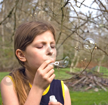 8 Year Old Blowing Bubbles stock photo, Pretty 8 year old Caucasian girl is blowing bubbles outdoors. by Valerie Garner