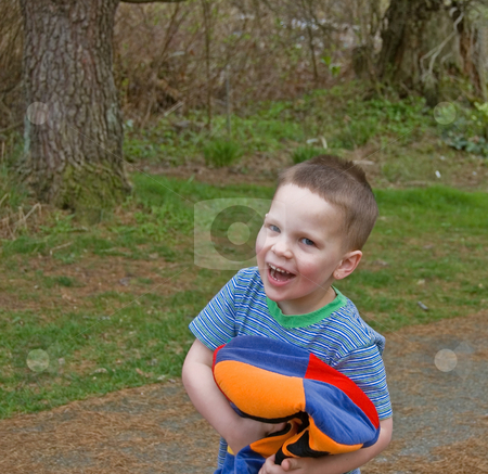 Little Boy Laughing and Playing With Colorful Hat stock photo, This little boy is laughing and playing with a very bright colorful hat in a candid facial expression of joy. by Valerie Garner