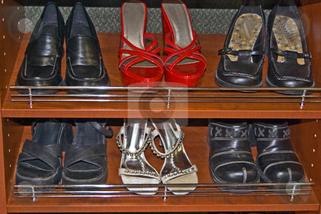 Closet of Shoes stock photo, A two row closet of shoes with red high heels, silver and several pair of black shoes in wood shelves. by Valerie Garner