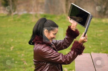 Young Professional Woman Frustrated at Laptop stock photo, This young, multi ethnic professional woman is working at the park with her laptop and is so frustrated, she's about to throw it. by Valerie Garner