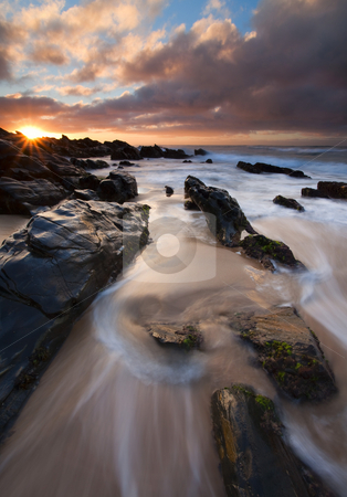 On the Rocks stock photo, The Ebbing tide flows around jagged rocks on Basham Beach at Sunrise by Mike Dawson