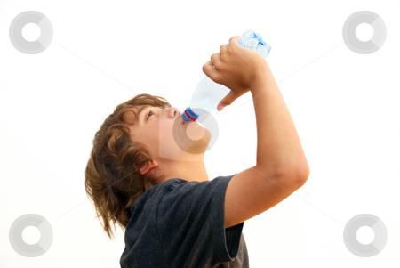 Teenage Boy Drinking Water stock photo, Teenage boy drinking water from a plastic bottle isolated on white background. by Denis Radovanovic