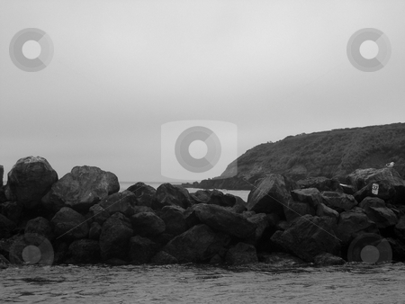 Rock wall on the water stock photo, Black and white image of rock wall on the water by Jaime Pharr