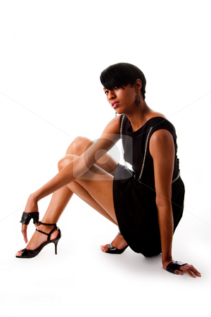 African fashion model stock photo, Beautiful modern classy African American female fashion model in black dress with silver chains and biker gloves sitting on the floor, isolated by Paul Hakimata