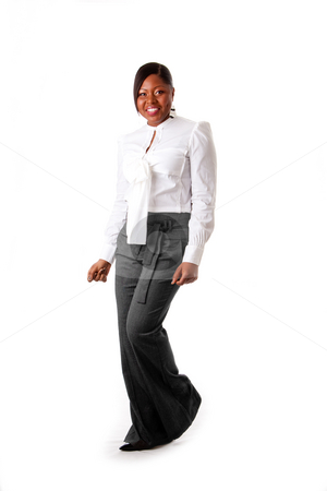 Happy African business woman stock photo, Beautiful African American business woman with attitude dressed in a white shirt and gray pants standing, dancing happy, isolated by Paul Hakimata