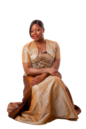 Beautiful African woman stock photo, Beautiful African American woman in brown with gold dress, sitting, isolated by Paul Hakimata