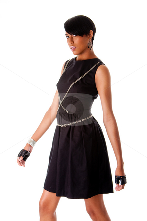 African fashion model stock photo, Beautiful modern classy African American female fashion model in black dress with silver chains and black biker gloves walking, isolated by Paul Hakimata