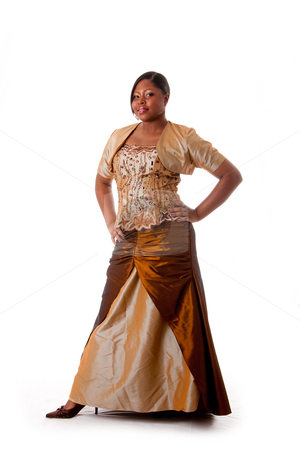 Beautiful African woman stock photo, Beautiful African American woman in brown with gold dress, hands on hips and standing, isolated by Paul Hakimata