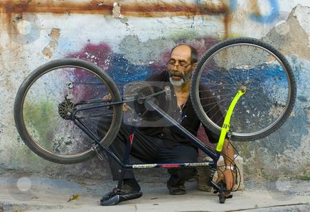 Fixing the bike stock photo, Turkish man fixing his bicycle in Ankara street by Kobby Dagan