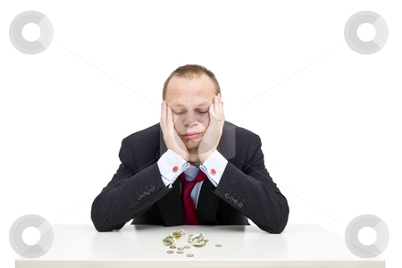Financial Crisis stock photo, A desperate businessman, with an unbuttoned collar and a loose nektie, looking depressingly at the few dollars in front of him on the table, illustrating the poor economic situation by Corepics VOF