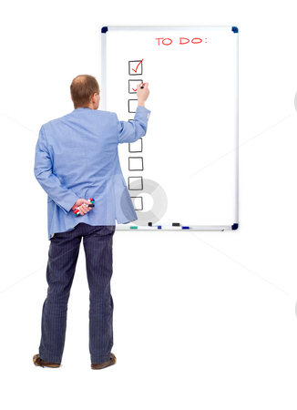 To Do List stock photo, A business man checking off his completed tasks from a to do list, written on a whiteboard by Corepics VOF