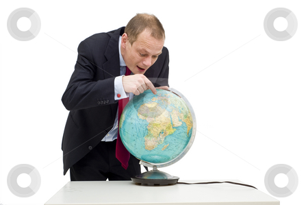 Discovering global business stock photo, A businessman discovering the potential of global business, visualised by his expression and pointing finger on the globe on the table in front of him. by Corepics VOF
