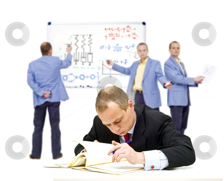Advanced learning stock photo, A manager, trying to understand some very complex theories, oblivious of the people in the background trying to explain it to him by Corepics VOF