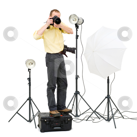 Studio photographer stock photo, A professional photographer standing on a flight case to get a higher angle in a studio, surrounded by three strobes by Corepics VOF