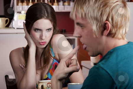 Woman flirting with uninterested male friend stock photo, Woman flirting with uninterested male friend in a coffee house by Scott Griessel