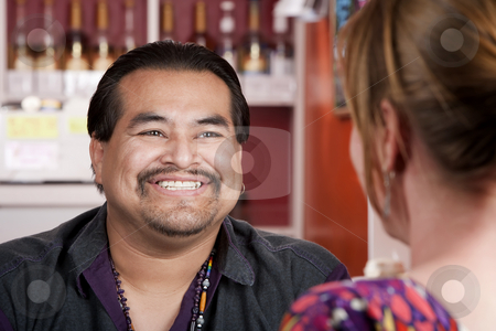 Native American man with female friend in restaurant stock photo, Handsome Native American man with female friend in a restaurant by Scott Griessel