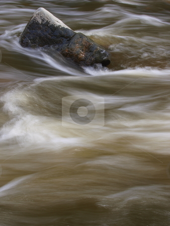 River Rock stock photo, Color image of a river rock with blurred water moving past it. by Michael Rice