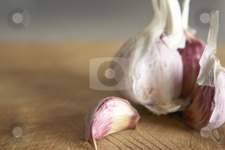 Garlic close up stock photo, Macro image of fresh garlic on rough wooden chopping board Shallow focus. by Gary Cookson